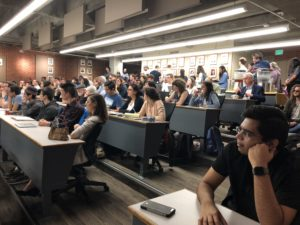Photo of a classroom of people sitting at rows of desks for an ExplOrigins meeting